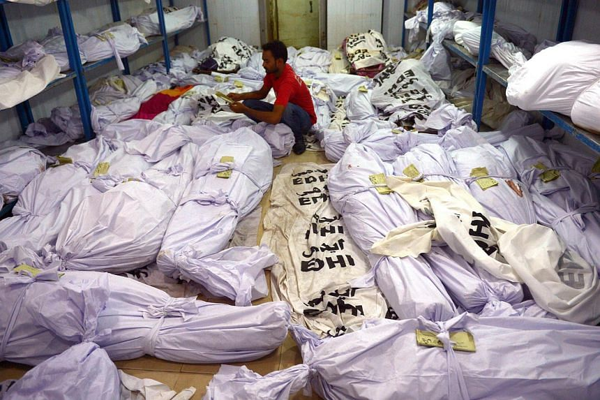A Pakistani volunteer puts a identification paper onto a body of a heatwave victim as other dead bodies are seen in the the cold storage of the Edhi morgue in Karachi.