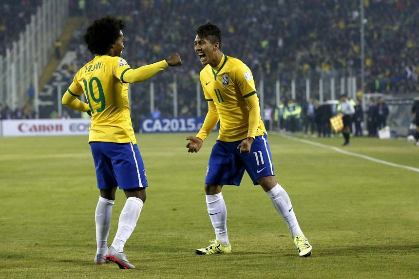 Brazil's Roberto Firmino (right) celebrates with teammate Willian after scoring during the Copa America 2015 Group C football match between Brazil and Venezuela.