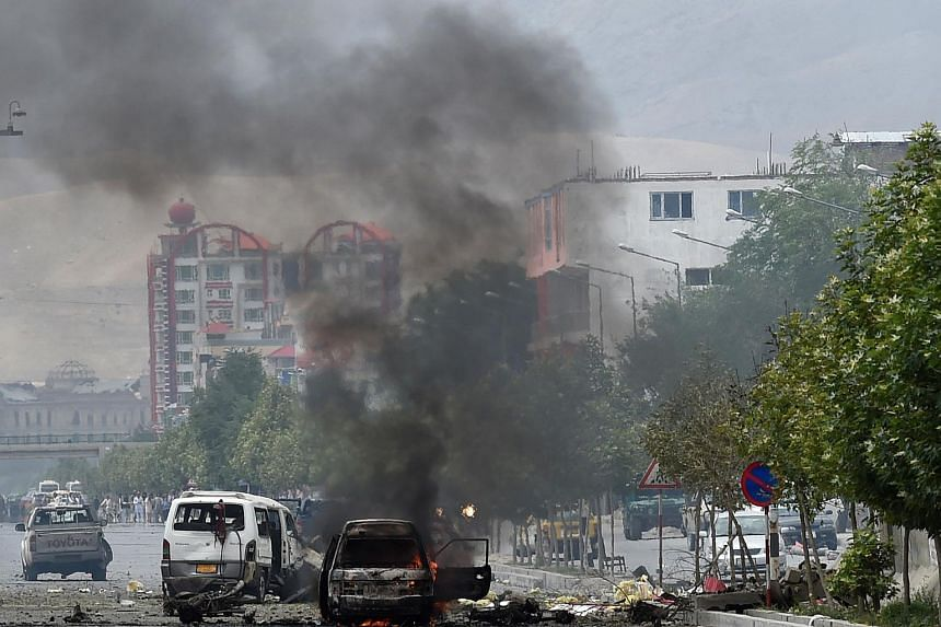 Smoke and flames rise from burning vehicles at the site of an attack in front of the Afghan Parliament building in Kabul on June 22, 2015.
