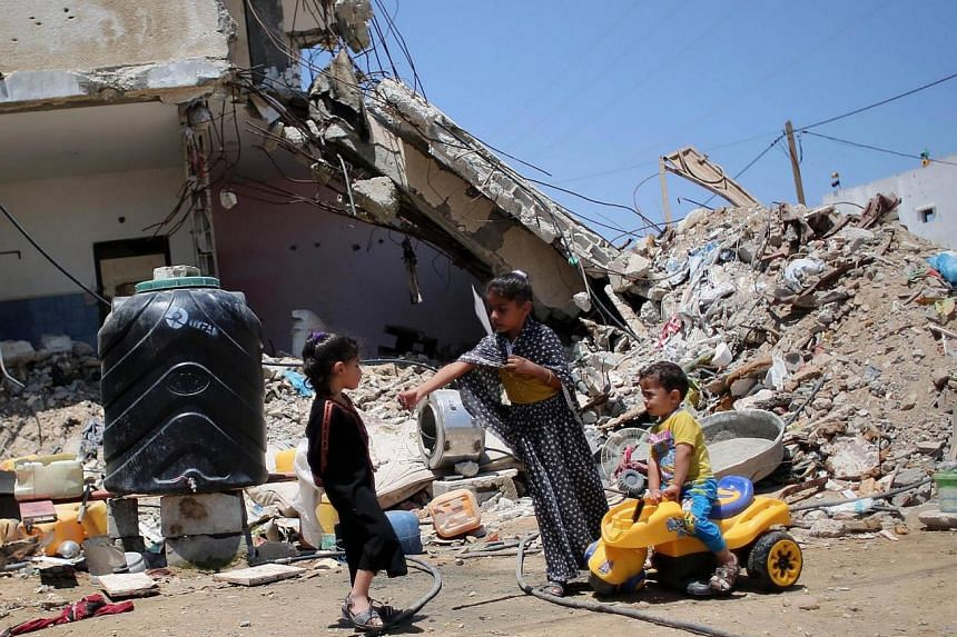 Palestinian children play in front of the rubble of buildings which were destroyed during the 50-day war between Israel and Hamas militants last year, in the village of Khuzaa in the southern Gaza Strip, on June 15, 2015. A UN report said that both I
