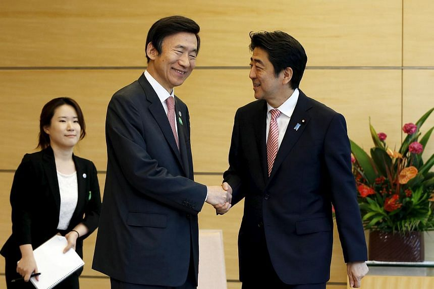 South Korea's Foreign Minister Yun Byung Se (centre) shakes hands with Japan's Prime Minister Shinzo Abe at the start of their talks at Mr Abe's official residence in Tokyo on June 22, 2015.