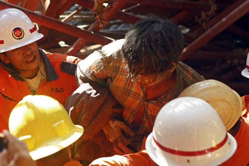 Myanmar firefighters rescue a construction worker after the scaffolding collapsed at the Pullman Hotel construction project in Mandalay, Myanmar on June 20, 2015.