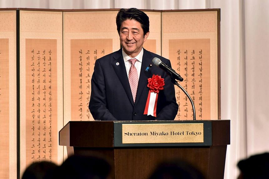Japan's Prime Minister Shinzo Abe smiles as he delivers a speech at the 50th anniversary ceremony for the normalizing of relations between Japan and South Korea.