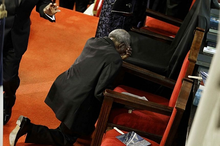 A parishioner prays at the empty seat of the Rev. Clementa Pinckney before services at the Emanuel African Methodist Episcopal Church in Charleston, South Carolina on Sunday. The church held its first service since a mass shooting left nine people de