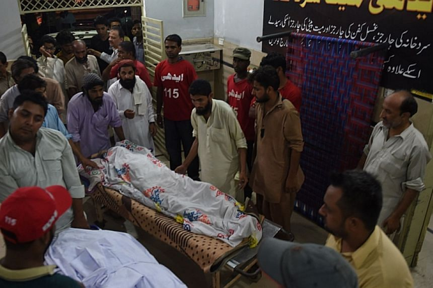 Volunteers (In red jerseys) and relatives shift the dead body of heatwave victims at the EDHI morgue in Karachi on June 21, 2015.