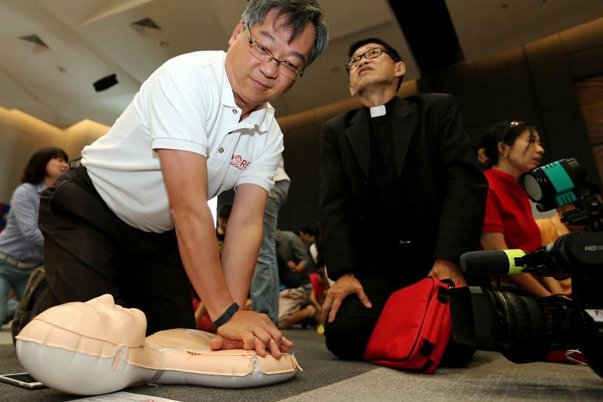 Health Minister Gan Kim Yong (left) and Reverend Derrick Lau at a simplified CPR training session at the Methodist Churchof the Incarnation. The training is being extended to religious organisations and workplaces.
