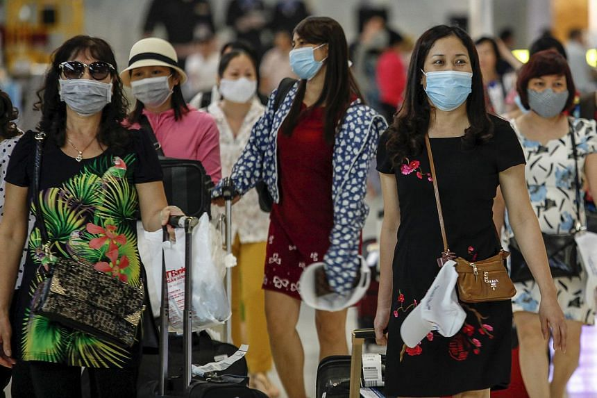 A group of tourists wear masks at Bangkok's Suvarnabhumi International Airport, June 21. Malaysia has stepped up health screenings at all entry points into the country since neighbouring Thailand reported its first case of Mers.