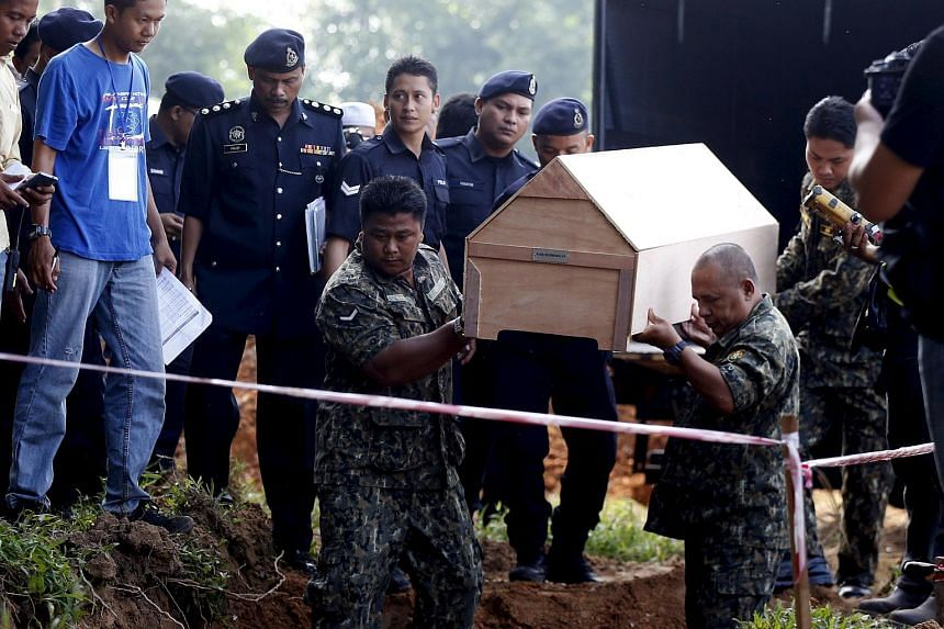 Malaysian police carry a coffin with unidentified remains of Rohingya people found at a traffickers camp in Wang Kelian last month, to be buried in a mass grave at a cemetery near Alor Setar, Malaysia.