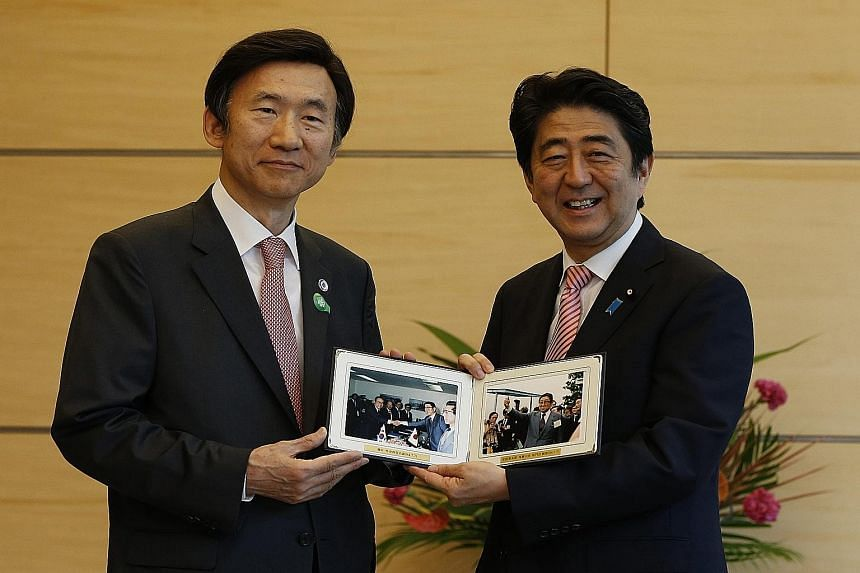 South Korean Foreign Minister Yun Byung Se (left) presenting Japanese PM Shinzo Abe with photos of Mr Abe's father, former foreign minister Shintaro Abe, taken in 1984, at their talks in Tokyo yesterday.
