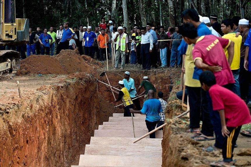 Workers in Kampung Tualang (above) preparing a pit yesterday for the reburial of remains believed to be those of Rohingya found at human-trafficking camps in jungles in northern Malaysia along the Thai border. (Left) Malaysian police and anti-smuggli