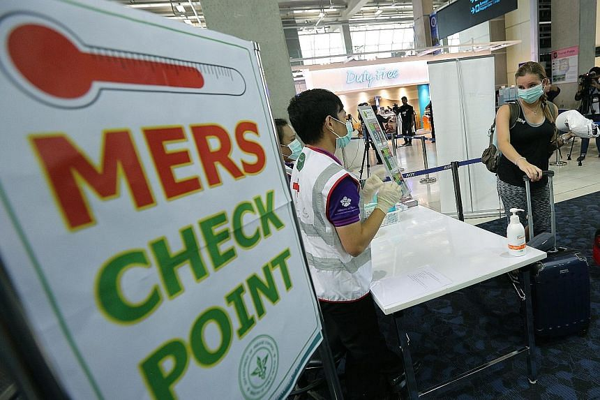 Passengers passing through a Mers health checkpoint at Bangkok's Suvarnabhumi airport on Sunday. Thermal scanners have been set up to screen visitors from the seven affected nations.