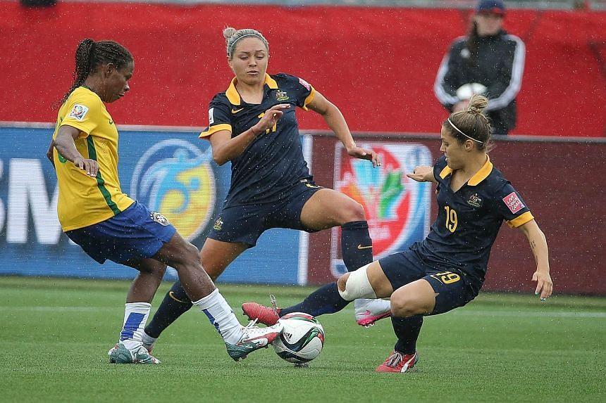 Australia forward and scorer Kyah Simon (centre) and midfielder Katrina Gorry combining to stop Brazil midfielder Formiga during the game.