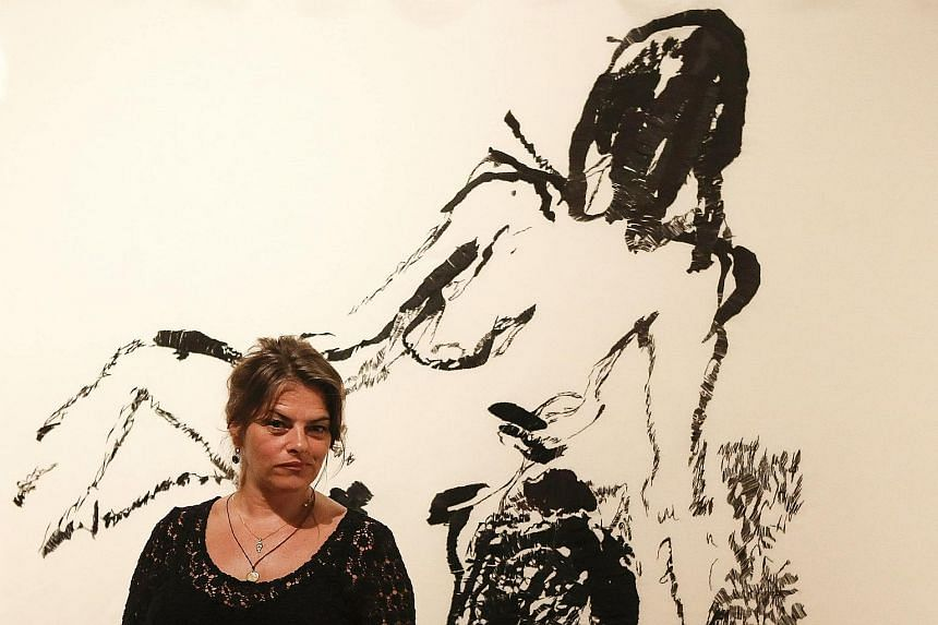 Artist Tracey Emin poses in front of her painting Distant Memory (left). Her most famous work is My Bed (far left), consisting of a rumpled bed surrounded by empty vodka bottles, cigarette packets and condoms, which sold at auction last year for $5 m
