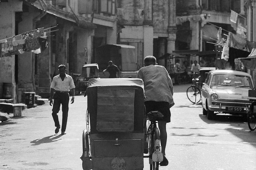 """On Our Way To Pasar Malam (1968, above), digital print on archival paper: Loke favours this shot of street vendors pushing their carts along Circuit Road near Aljunied, as it is """"layered"""". He explains: """"In the foreground, you have the hawkers. By the"""