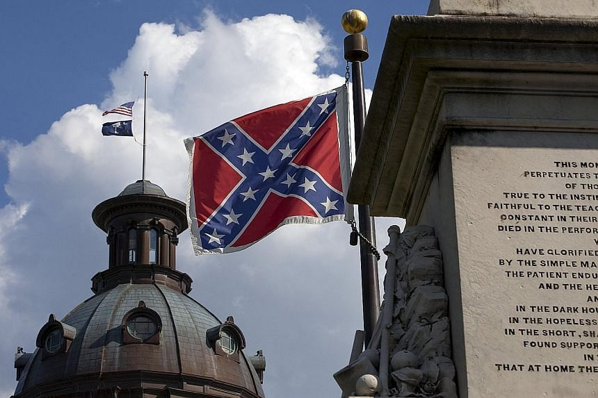 The Confederate battle flag (right) on the grounds of the South Carolina State House against the backdrop of the US flag and South Carolina state flag flying at half mast in the wake of the Charleston murders last week.