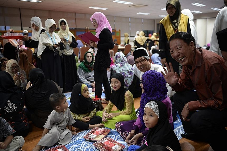 Deputy Prime Minister Teo Chee Hean (right) and Minister-in-charge of Muslim Affairs Yaacob Ibrahim (second from right) chatting with young Muslims breaking fast at Mujahidin Mosque in Commonwealth yesterday.