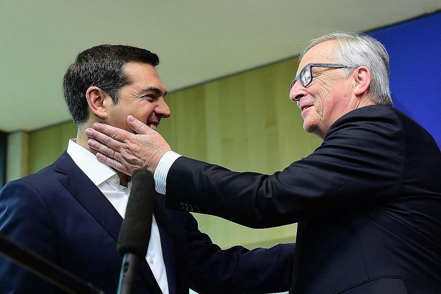 """European Commission president Jean-Claude Juncker (right) greeting Greek PM Alexis Tsipras with a playful slap. Mr Juncker warned that a deal """"was not there yet"""". Officials say there had been confusion overnight with Greece apparently initially sendi"""