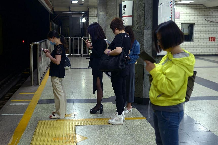 People looking at their mobile phones as they wait for a train at a subway station in Beijing on May 7, 2015. China has approved two subway system projects worth 129.8 billion yuan (S$27.8 billion), according to documents published on Tuesday, June 2