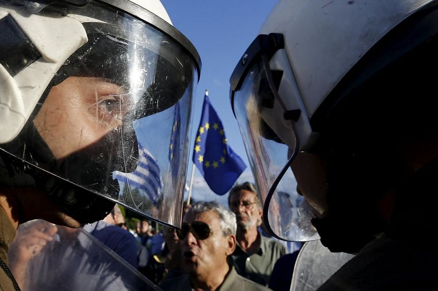 Riot policemen stand between anti-austerity and pro-EU protesters in front of the parliament building during a rally calling on the government to clinch a deal with its international creditors and secure Greece's future in the Eurozone, in Athens, Gr