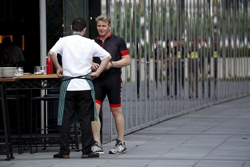 British chef Gordon Ramsay talks to his staff as breakfast is prepared at his newly-opened restaurant after an exploratory tour around the city with cycling enthusiasts in Singapore.