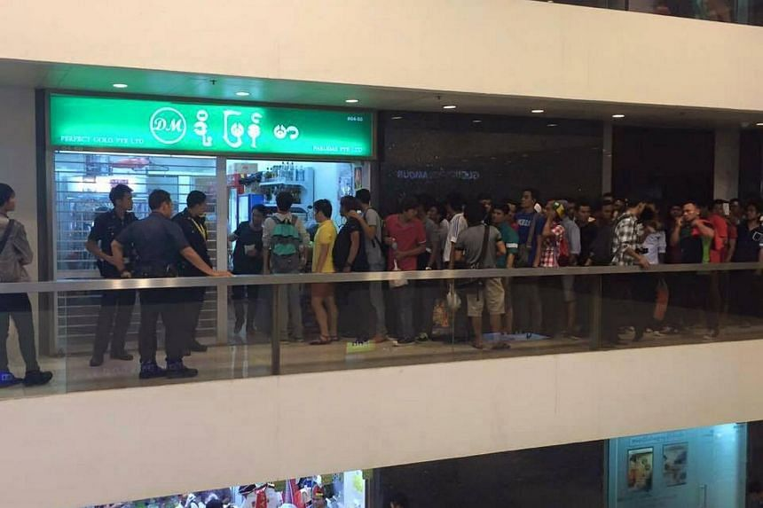 Customers queuing up outside Doe Myanmar in Peninsula Plaza to buy tickets to the SEA Games football final between Thailand and Myanmar.