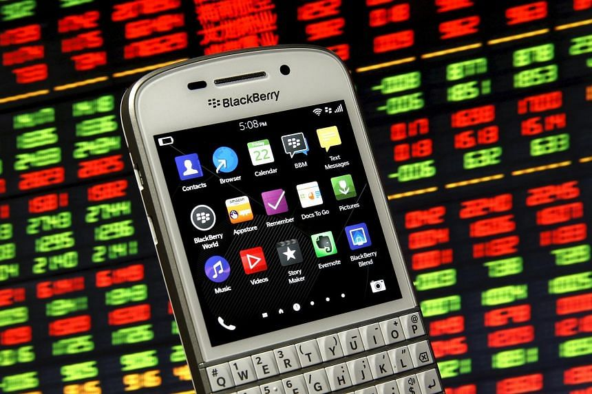 A Blackberry Q10 smartphone is seen in front of a displayed stock graph.