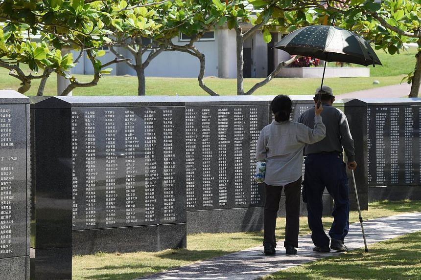 An elderly couple walking beside a monument commemorating those who died in the battle of Okinawa, on June 19, 2015.