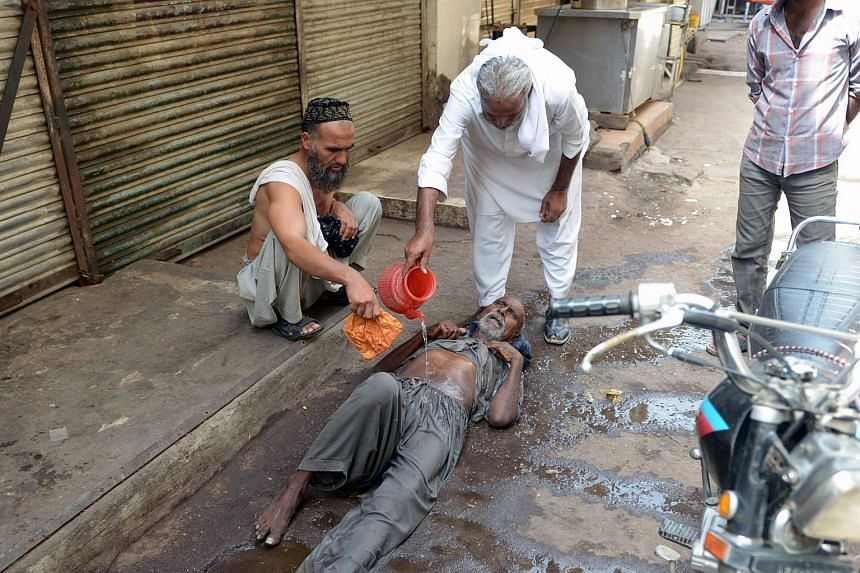 Pakistani residents helping a heatstroke victim at a market area during a heatwave in Karachi on June 23, 2015. More than 450 people have died in the three-day heatwave hitting southern Pakistan, officials said on Tuesday.
