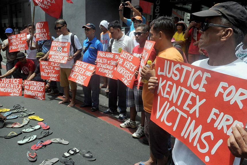 Protesters hold placards during a rally to call for justice for the victims of the fire that gutted the Kentex footwear factory the day before, in Manila on May 14, 2015. The families of the 57 victims of the fire have dropped their claims for a sett