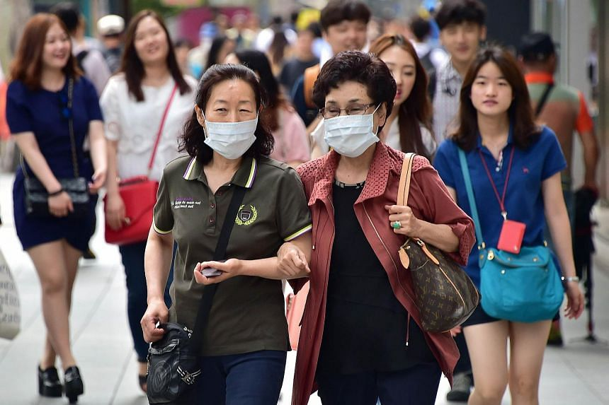 Women wearing face masks in a shopping district in Seoul on June 19, 2015.