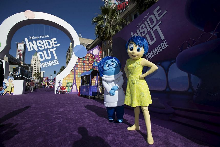 Joy and Sadness, characters of the animation film Inside Out, pose at its premiere at El Capitan theatre in Hollywood, California.