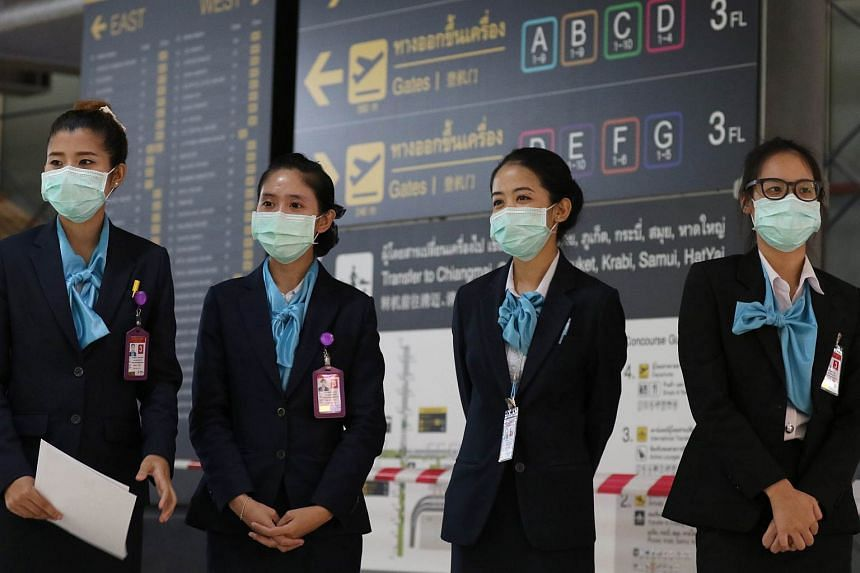 Airport staffs wear protective masks against Middle East Respiratory Syndrome (Mers) while on duty at Suvarnabhumi airport in Bangkok, Thailand.
