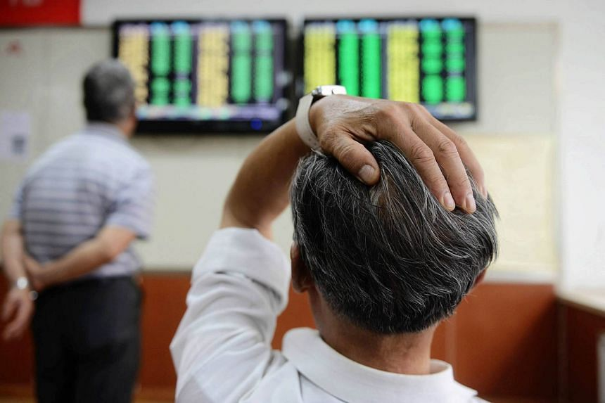Chinese stock investors react as they check the prices on the board at a securities firm in Qingdao, in China's Shandong province on June 19, 2015.