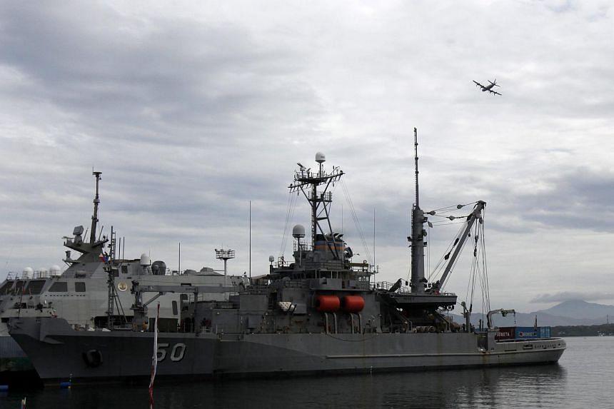 A Japanese Maritime Self-Defense Force P3C patrol plane flies over US warship USNS Safeguard (T-ARS-50).