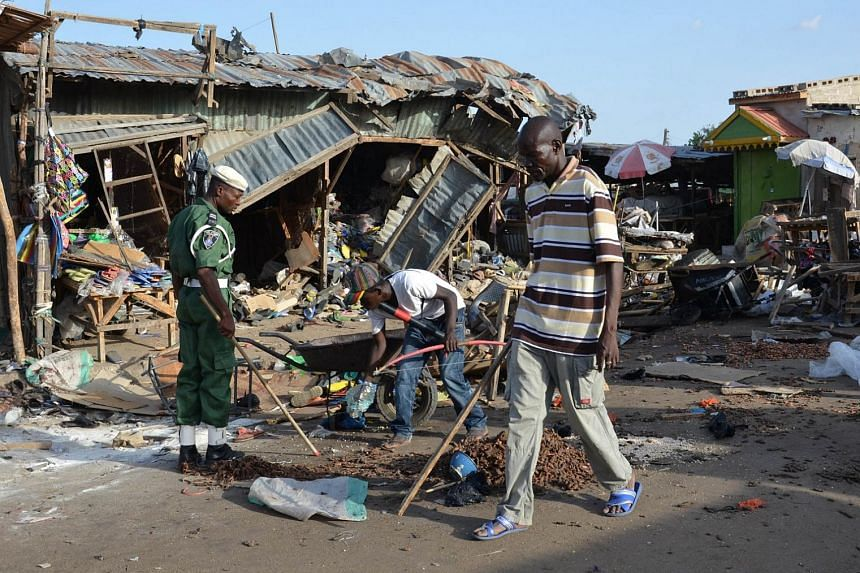 A man walks past a the scene of a bombing after at least 20 people were killed when a young female suicide bomber detonated her explosives at a bus station in Maiduguri, northeast Nigeria, on Monday in an attack likely to be blamed on Boko Haram. The