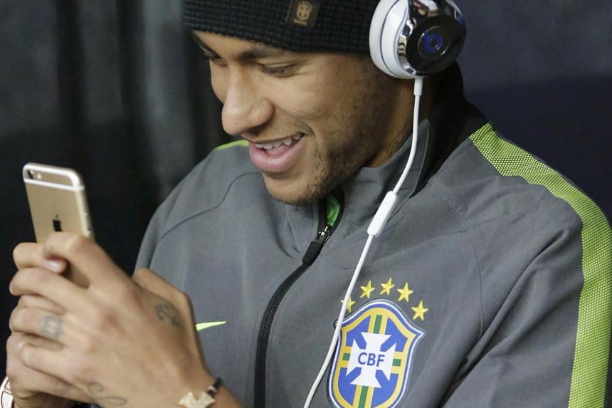 Brazil's Neymar, who is suspended for the rest of the tournament, uses his mobile phone as he arrives with his team for their first round Copa America 2015 soccer match against Venezuela at Estadio Monumental David Arellano in Santiago, Chile, on Sun