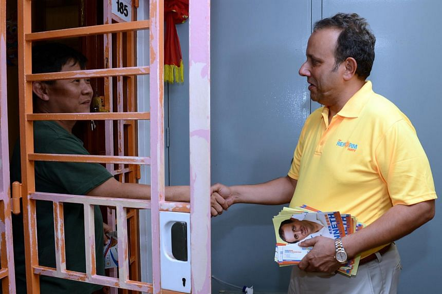 Reform Party's Kenneth Jeyaretnam (right) shaking hands with a resident during a house-to-house visit.