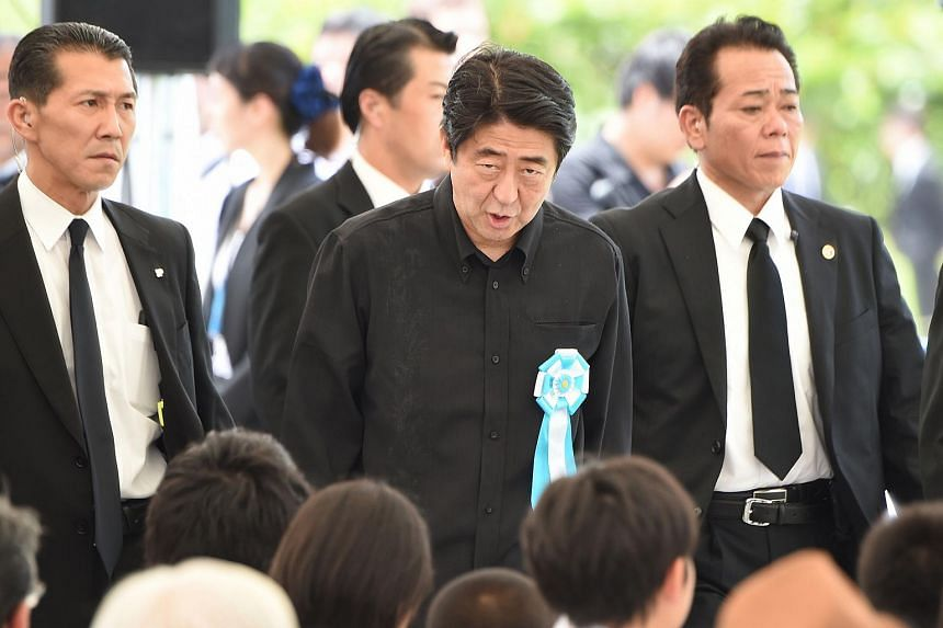 Japanese Prime Minister Shinzo Abe (centre) greets attendees as he arrives for a memorial service for those who died in the Battle of Okinawa during World War II on June 23, 2015.