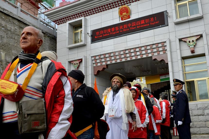 The first group of Indian Buddhist pilgrims passing through the Nathu La Pass yesterday. The new land crossing will halve the pilgrimage time from more than 20 days. Its opening was agreed on by Chinese President Xi Jinping and Indian Prime Minister
