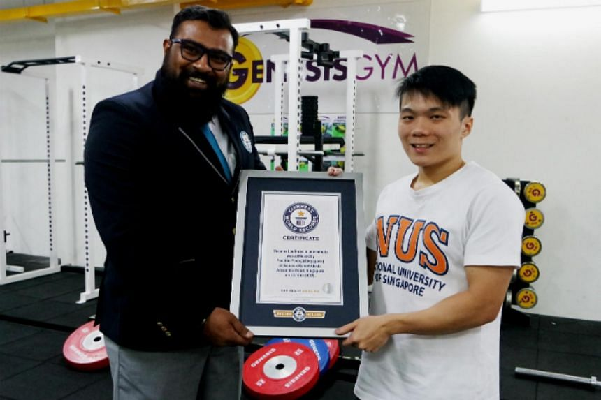 Mr Yeo Kim Yeong standing with his certificate for the Guinness World Records title for most pull ups in one minute.