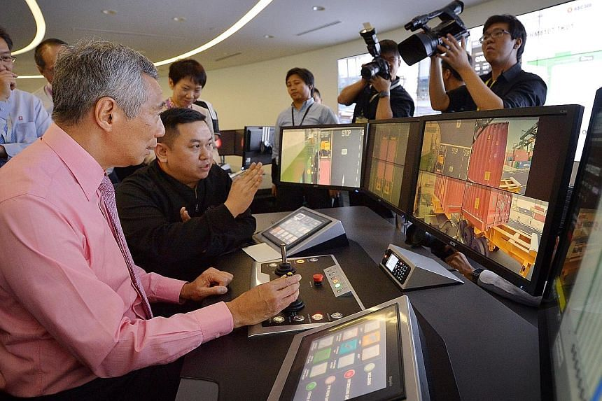 PM Lee Hsien Loong operating a crane from the Automated Crane Operations Centre, guided by assistant operations executive Larry Wong (seated, in black), yesterday. The cranes, which can be operated remotely, help save on manpower and increase product