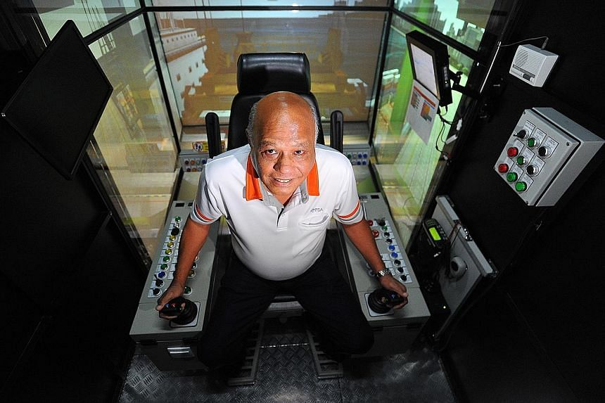 PSA Institute trainer Martin Verghese, seen here in a crane simulator, was among the first group of quay crane operators. PM Lee Hsien Loong paid tribute to workers like him yesterday.