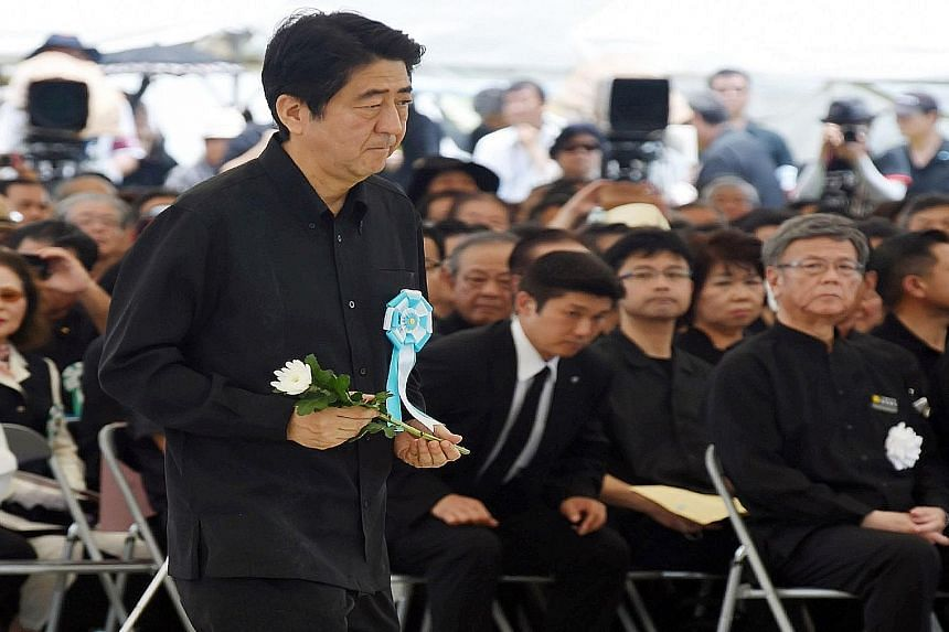 """Japanese Premier Shinzo Abe offering a flower at a ceremony to remember the Battle of Okinawa yesterday, as Okinawa Governor Takeshi Onaga (right) looked on. There were cries for Mr Abe to """"go home"""". Residents of the island, which suffered Japan's on"""