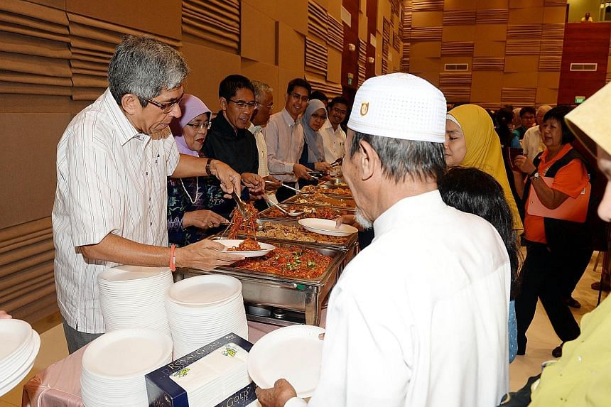 Helping to serve low-income workers and their families at a breaking-of-fast session are (from left) Dr Yaacob Ibrahim, Madam Halimah Yacob, Dr Maliki Osman, Mr Hawazi Daipi, Associate Professor Muhammad Faishal Ibrahim, Dr Intan Azura Mokhtar and Mr