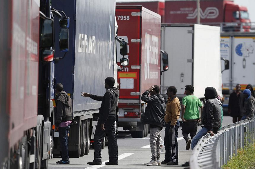 Migrants gathering near a line of lorries waiting on the motorway which leads to the Channel Tunnel terminal in Calais.