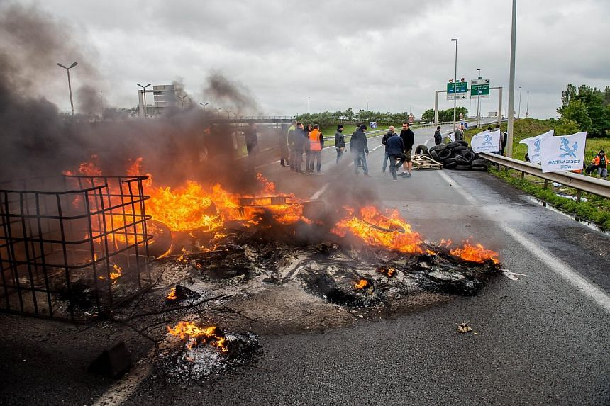Employees of the French company My Ferry Link, a cross-channel ferry service, stand in front of tyres set on fire as they block the access to the Channel Tunnel on June 23, 2015 in Calais, northern France.