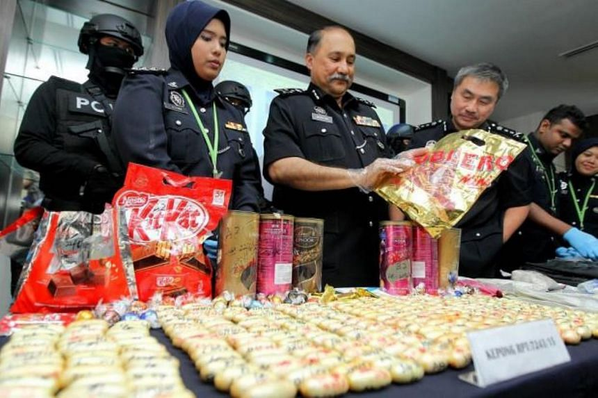 Malaysia's Bukit Aman Narcotics criminal investigation department director Mohd Mokhtar Mohd Shariff holding up a bag of seized drugs disguised as chocolates.