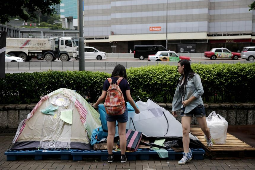 Two protesters pack up their tent at the last remaining pro-democracy site in the Admiralty district of Hong Kong on June 23, 2015.