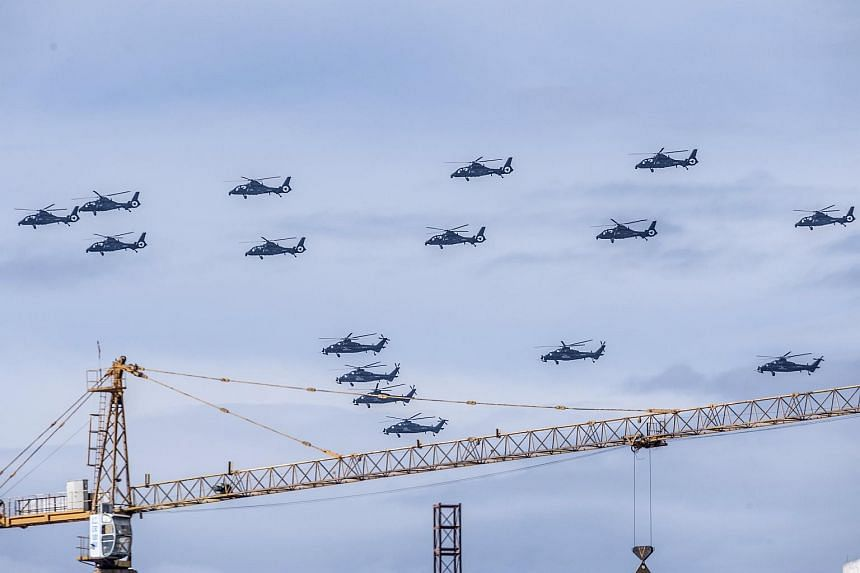 Helicopters fly in formation above a construction site in Beijing during a training session for the parade marking the 70th anniversary of the end of World War II, on June 12, 2015. China has extended an invitation to former soldiers living in Taiwan