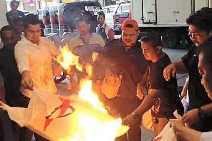 Umno members setting fire to two opposition Democratic Action Party (DAP) flags outside the Komtar building in Penang on June 23, 2015.